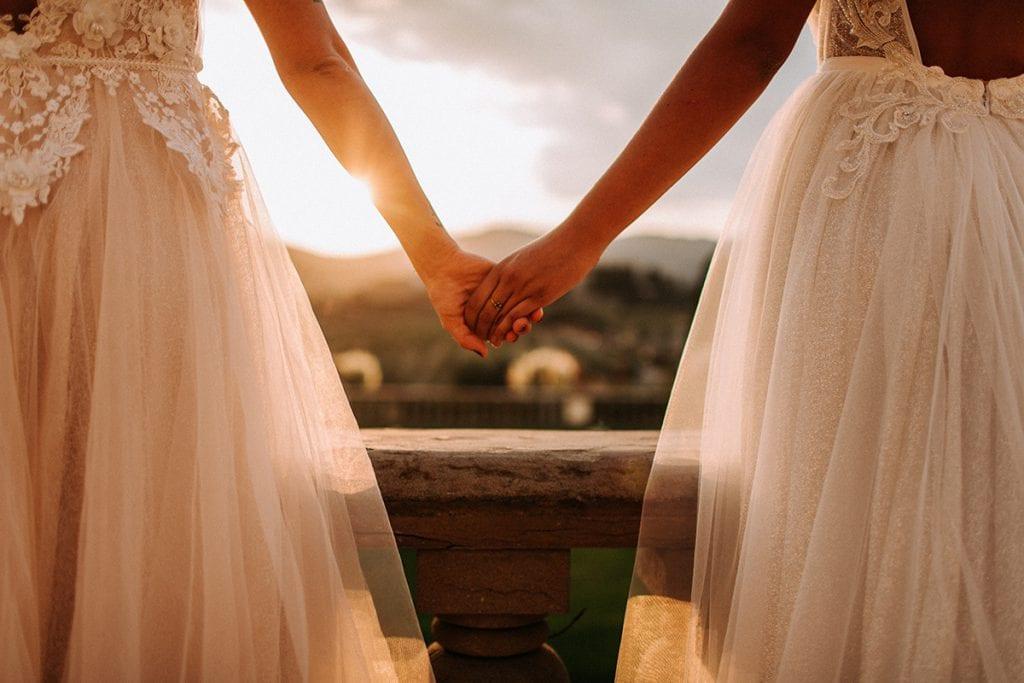 2 brides tuscany wedding holding hands